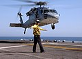 US Navy 070214-N-3211R-017 Aviation Boatswains Mate Handler Airman Noah Timmons stationed aboard the amphibious assault ship USS Bonhomme Richard (LHD 6), gives the clear to launch signal to a MH-60S Seahawk.jpg