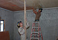 US Navy 071004-N-1003P-001 Utilitiesman 3rd Class Brian Sievers, left, holds a four-by-four so Builder Constructionman Ben Reed can put up ceiling tile in the administration building.jpg