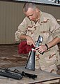 US Navy 081217-N-2555T-006 Gunner's Mate 3rd Class James Miller inspects his weapon while cleaning it.jpg