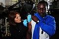US Navy 090518-N-3946H-016 Hospital Corpsman 2nd Class Jennifer Ross administers an anthrax vaccination to Aviation Boatswain's Mate (Handling) Airman Michael Glover in the hangar bay of the aircraft carrier USS Nimitz (CVN 68).jpg
