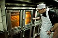 US Navy 111211-N-GC412-437 Culinary Specialist Seaman Matthew Ryback checks on apple tarts in the oven in the bakeshop aboard the Nimitz-class airc.jpg