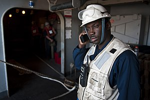 US Navy 111221-N-BT887-089 Boatswain's Mate 1st Class Corey Broadnax listens for commands while supervising the connection of a double-probe refuel.jpg