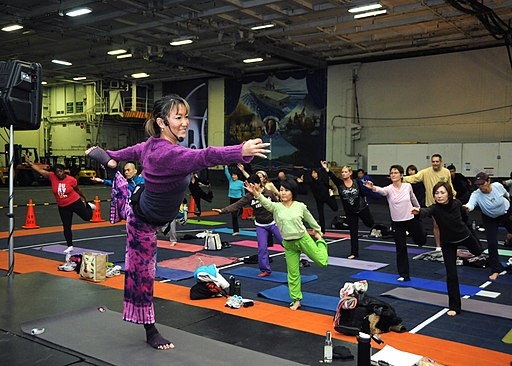 US Navy 120213-N-ZT599-068 Chieko Koymama, a yoga instructor with morale, welfare and recreation conducts a yoga class in the hangar bay aboard the