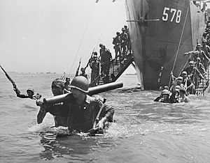 Men wearing military uniforms and carrying equipment walking down ramps from a ship into the sea