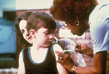 English: A nurse vaccinating a child. Français...