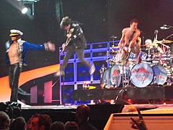 Van Halen performing onstage: David Lee Roth is wearing a sea captain's outfit with his arms outstretched, Woflgang Van Halen is jumping in the air with his bass guitar, Eddie Van Halen is also jumping while playing guitar, and Alex Van Halen is behind them drumming