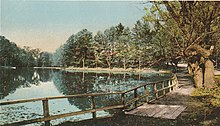 A colorized image of a path running along the bank of a lake and up towards a dirt road. The lake is still and glassy, and trees and a fence rest along its banks.