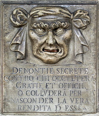 "Tax evasion - A ""Lion's Mouth"" postbox for anonymous denunciations at the Doge's Palace in Venice, Italy. Text translation: ""Secret denunciations against anyone who will conceal favors and services or will collude to hide the true revenue from them."""