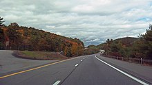 A view of a divided highway from its righthand roadway, with two lanes separated by a dashed white line. There is almost no other traffic; the surrounding area is wooded with some autumn color visible. Ahead the roadways curves by a hill and disappears.