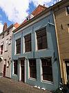 foto van Huis met brede gepleisterde lijstgevel, hoge kap en dakkapel. Twee voordeuren, gekoppeld. Kelder