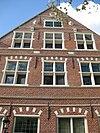foto van Huis met vernieuwde puntgevel, waaraan natuurstenen vensterkozijnen, een fronton, twee medaillons met koppen, alsmede twee pilasters