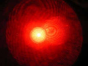 English: View into a lens widened red laserbea...