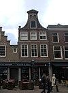 foto van Pand met klokgevel met horizontale banden, bekroond door driehoekig fronton met vazen op de hoeken