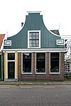 foto van Huis met ingezwenkt van zijmeanders voorzien voorschot boven een bakstenen pui