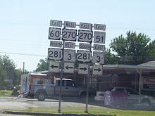 An array of road signs, with signs for US-60, US-270, US-281, and SH-3 pointing left, and signs for US-270, US-281, SH-3, and SH-51 pointing right.