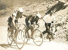 Photographie en noir et blanc de deux cyclistes montant un col, l'un poussant l'autre, un homme courant à leur côté.