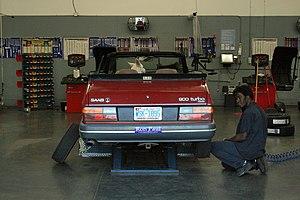 Automobile repair shop - A Saab 900 Turbo convertible undergoing regular maintenance at a Sam's Club service garage