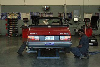 Automobile repair shop - A Saab 900 Turbo convertible undergoing regular maintenance at a Sam's Club service garage