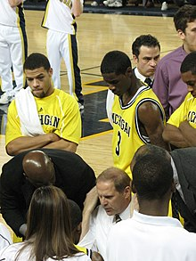 basketball players in maize uniforms have their attention on a man in a white shirt who is seated or kneeling below them. They look over his shoulders as other people look on.