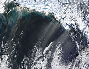 Climate of Alaska - Natural-colour satellite image showing thin plumes of beige dust blowing off the Alaskan coast.