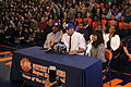 20131115 Jahlil Okafor's father, aunt and coach during verbal commitment in hats.JPG