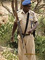 ASC Leiden - van de Bruinhorst Collection - Somaliland 2019 - 4592 - Grinning police officer with a Kalashnikov gun near the caves with rock paintings of Laas Geel.jpg
