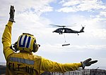 A Sailor directs an MH-60S Sea Hawk during an at-sea ammunition onload with USNS Wally Schirra. (30441316232).jpg