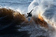 Photo of surfer wiping out with arms outstretched and body parallel to surface