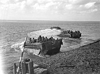 An amphibious vehicles carrying troops drives up out of the water onto a beach. A similar vehicle is yet to reach the shore