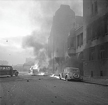 A car on fire and smoking heavily next to the Milk Centre office building in Central Helsinki after a Soviet aerial bombing.