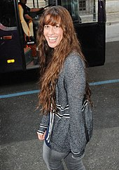 A picture of a woman who is smiling. She is walking on a street and she is looking back over her left shoulder. She wears a grey sweater with some black frames, and jeans of the same colour. In the background a black bus is visible.
