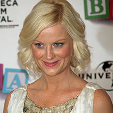 A shot from the shoulders up of a blond woman with blue eyes wearing a white and green dress, smiling and looking at something outside the image.