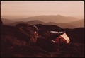 BACKPACKER CAMP AT THE SUMMIT OF ALGONQUIN MOUNTAIN AT SUNSET, NEAR LAKE PLACID, NEW YORK, IN THE ADIRONDACK FOREST... - NARA - 554515.tif