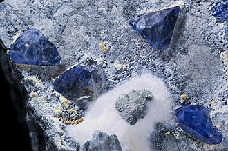 Barium - Benitoite crystals on natrolite. The mineral is named for the San Benito River in San Benito County where it was first found.