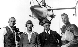 Half-length informal portrait of four men with an aircraft engine and struts above and behind them