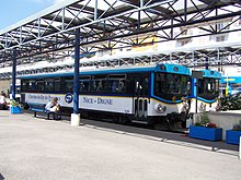 Vue de deux bus en gare routière sous une structure métallique avec le quai en premier plan.