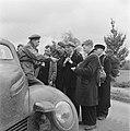 Canadese soldaat deelt sigaretten uit aan een groep mannen met ransels of rugzak, Bestanddeelnr 900-2898.jpg