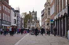 A view down a pedestrianised street with walkers and shops each side with a sixteenth century buttercross in the distance