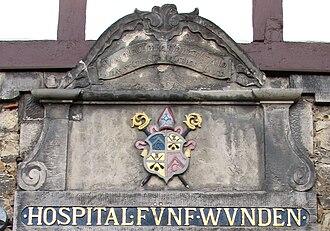 Chronogram - Chronogram above the entrance of the Hospital of the Five Wounds in Hildesheim, Germany.  CVra BonIfaCII, PrIMo, QVo PraefVIt Anno Abbas SpeCtatos CoLLoCat Hos CeLares. 1770.