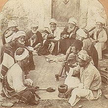 An old photo of a dozen old and middle-aged men sitting on a ground around a mat. A man in front sits next to a mortar and holds a bat, ready for grinding. A man opposite to him holds a long spoon.
