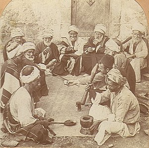 Monochrome photograph of men with turbans and facial hair reclining on a mat. In the foreground a man uses a mortar and pestle, while the men in the back have cups in their hands.
