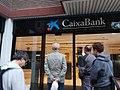 Cola ante una entidad de CaixaBanc en el Eixample de Barcelona.jpg