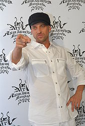 A white man in a white shirt with sleeves rolled up and a black baseball cap.  He is pointing at something in front of him with his right hand.