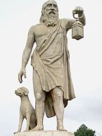 Stone statue of a bearded man in ancient Greek dress holding a lantern. A sculpted dog sits at his side.