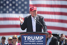 "Trump speaking in front of an American flag behind a podium, wearing a black suit and red hat. The podium sports a blue ""TRUMP"" sign."