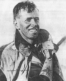 Half portrait of young grinning man in flying suit