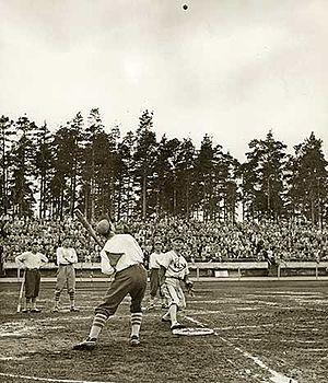 """Pesäpallo - Pesäpallo match in 1958 in Jyväskylä, with Eino Kaakkolahti pitching a very tall """"tolppa""""."""