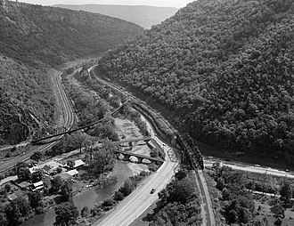 Western Maryland Railway - Eckhart Junction in the Cumberland Narrows, 1970. The masonry arch bridge over Wills Creek was built by the Maryland Mining Company in 1860 as part of the Eckhart Branch Railroad. Beyond the masonry bridge is a viaduct for the State Line Branch