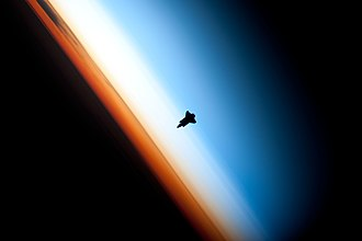 Atmosphere of Earth - Space Shuttle Endeavour orbiting in the thermosphere. Because of the angle of the photo, it appears to straddle the stratosphere and mesosphere that actually lie more than 250 km below. The orange layer is the troposphere, which gives way to the whitish stratosphere and then the blue mesosphere.