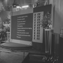 Black and white photograph of the scoreboard in 1958; the running order numbers and song titles of the competing entries are printed on the left-hand side of the scoreboard, and rotating numbers on the right-hand side show the allocation of points to each song as each country's jury is called, and a total of all points received; song titles are sorted by order of appearance, with the first song to be performed appearing at the top of the scoreboard.